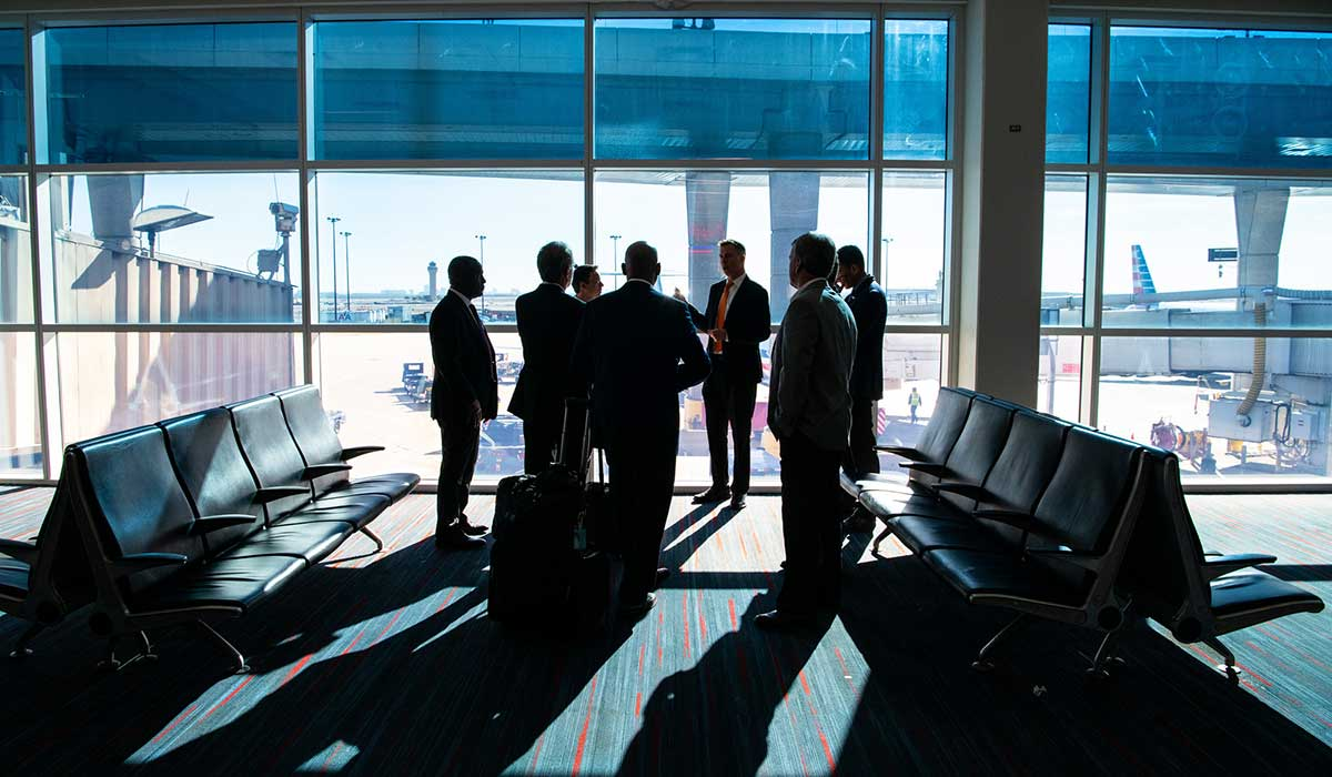 Eight men stand at an airport gate in discussion. Aircraft are visible through the window outside.