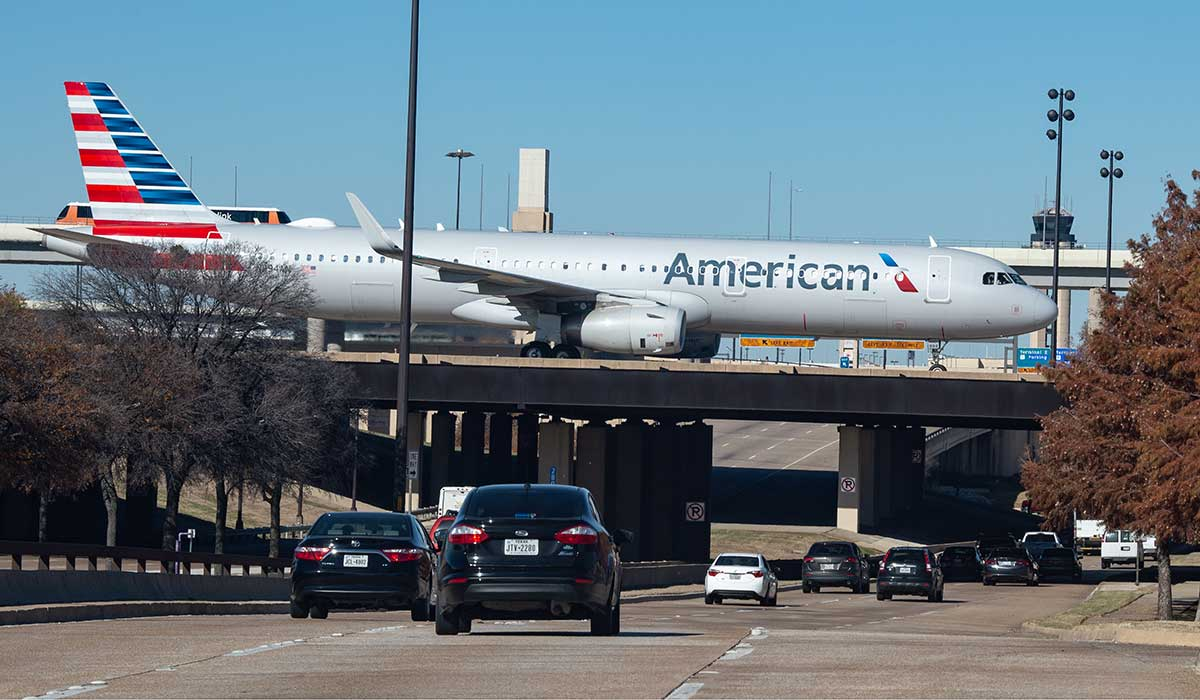 An airplane moves along a taxiway positioned on an overpass while several vehicles drive under. The airport light rail and air traffic control tower are visible in the background.